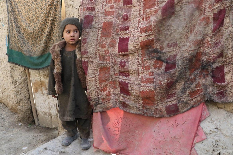 طفل أفغاني يقف أمام خيمة أسرته المصنوعة من بقايا أقمشة في أحد ضواحي كابل (الأناضول)