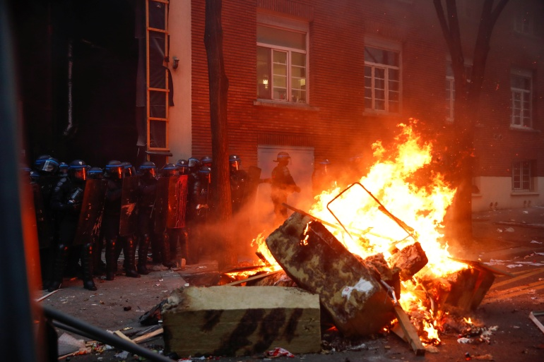 الشرطة تتحصن خلال المواجهات في باريس (رويترز)
