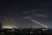 Israel's Iron Dome missile defence system (L) intercepts rockets (R) fired by the Hamas movement from Gaza city towards Israel early on May 16, 2021. - Israel pummelled the Gaza Strip with air strikes, killing 10 members of an extended family and demolishing a building housing international media outlets, as Palestinian militants fired back barrages of rockets. (Photo by MOHAMMED ABED / AFP) (AFP)