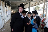 Ultra-Orthodox Jewish men and youths look at a mobile phone as they stand near the site where dozens were crushed to death in a stampede at a religious festival, as the country observes a day of mourning, at Mount Meron, Israel May 2, 2021. REUTERS/Amir Cohen (رويترز)