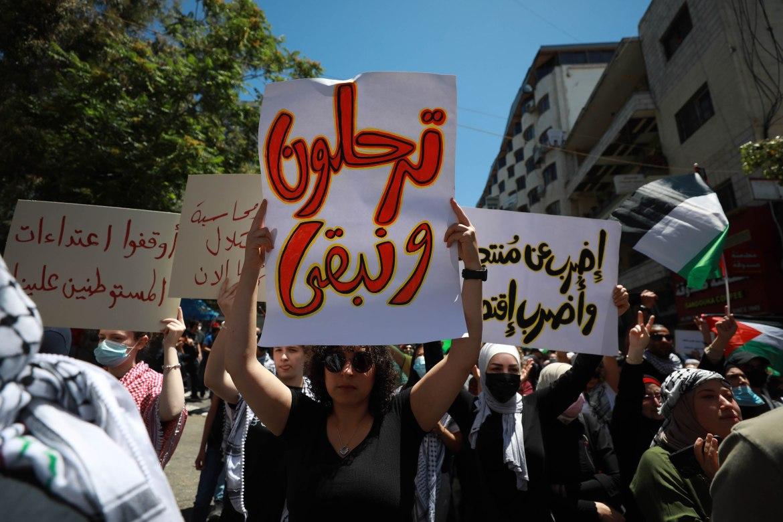 جانب من اللافتات التي رفعها المتظاهرون في رام الله يوم الإضراب (الأناضول)