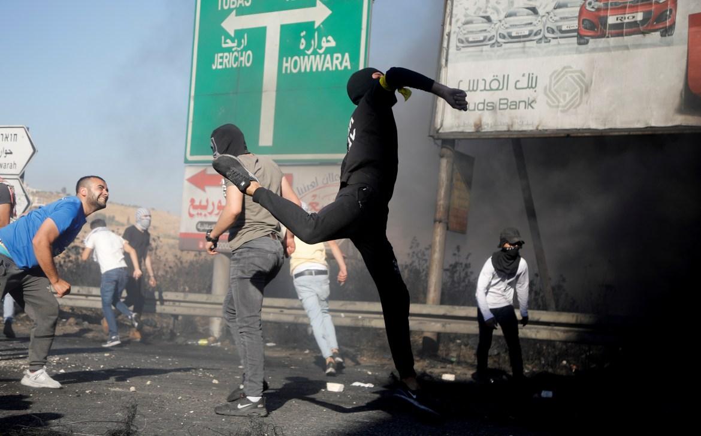 فلسطينيون يرشقون جنود الاحتلال بالحجارة عند حاجز حوارة خلال الإضراب الذي استبقه جيش الاحتلال بوضع أسلاك شائكة في محيط الحاجز الواقع جنوب نابلس لعزل المنطقة عن محيطها (رويترز)