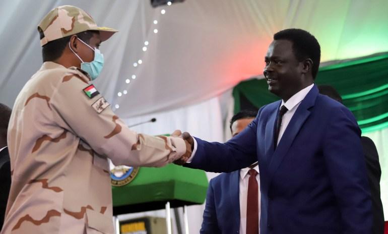 الفريق محمد حمدان دقلو (يمين) ومني مناوي بعد توقيع اتفاق السلام بين الفصائل المسلحة والحكومة في جوبا (رويترز)