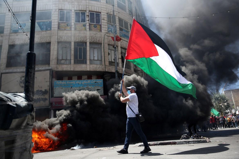 متظاهر فلسطيني يلوح بعلم فلسطين خلال اشتباكات مع قوات الاحتلال الإسرائيلي في وسط مدينة الخليل بالضفة الغربية المحتلة (الأوروبية)