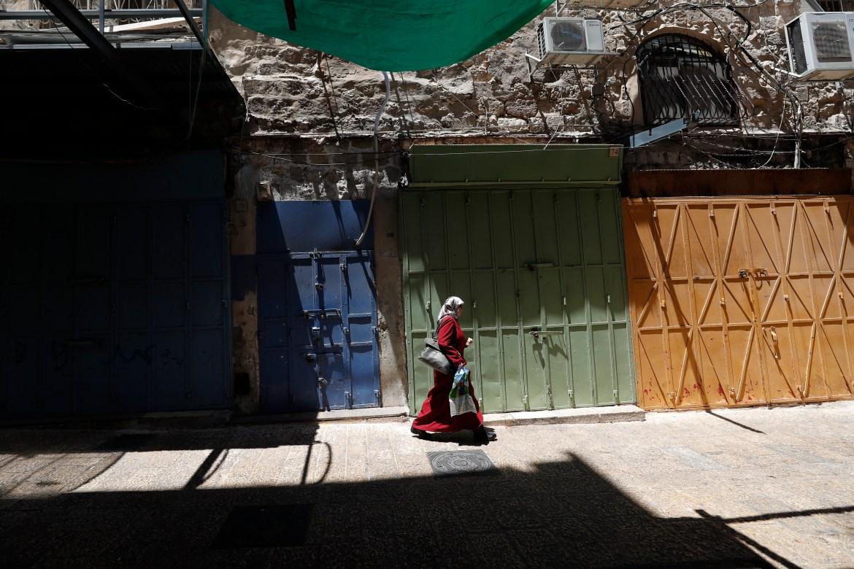 امرأة فلسطينية تمرّ في أزقة خالية من المارة في البلدة القديمة بالقدس المحتلة خلال الإضراب العام الذي لاقى تجاوبا واسعا غير مسبوق (الأوروبية)