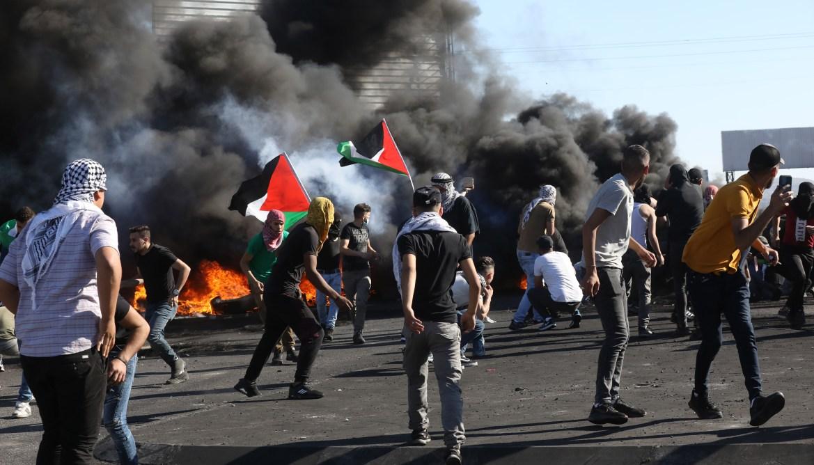 متظاهرون فلسطينيون يرشقون قوات الاحتلال الإسرائيلي بالحجارة خلال مواجهات عند حاجز حوارة بالقرب من مدينة نابلس بالضفة الغربية المحتلة التي لبت دعوة الإضراب، وأفاد مسعفون محليون بأن 25 فلسطينيا على الأقل أصيبوا خلال تلك الاشتباكات (الأوروبية)
