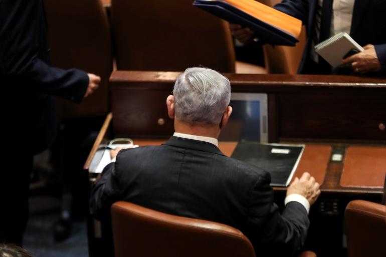 بنيامين نتنياهو يجلس في الكنيست الإسرائيلي في مقعد رئيس الوزراء الذي لم يعد له (رويترز)