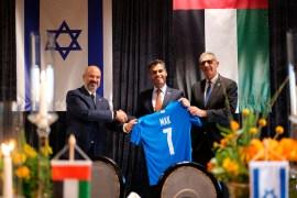 سفير الإمارات (وسط) ممسكا بقميص المنتخب الإسرائيلي الذي أهدي له (مواقع التواصل)