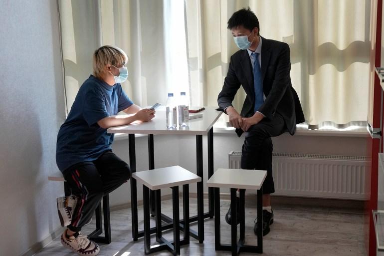وو هوان (يسار) وخطيبها الصيني وانغ جينغيو يجلسان معًا في منزل آمن في أوكرانيا نهاية يونيو/حزيران الماضي (أسوشيتد برس)